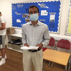 A Level student holding exam results wearing covid mask