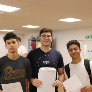 three teenage boys holding their GCSE Results